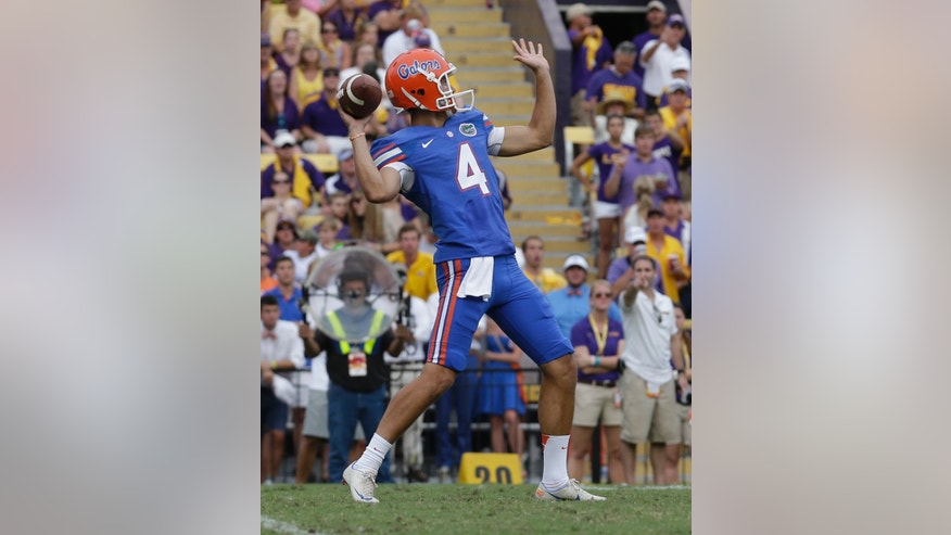 Florida punter Kyle Christy (4) passes on a fake punt in the second half of an NCAA college football game against LSU in Baton Rouge, La., Saturday, Oct. 12, 2013.  LSU won 17-6. (AP Photo/Gerald Herbert)