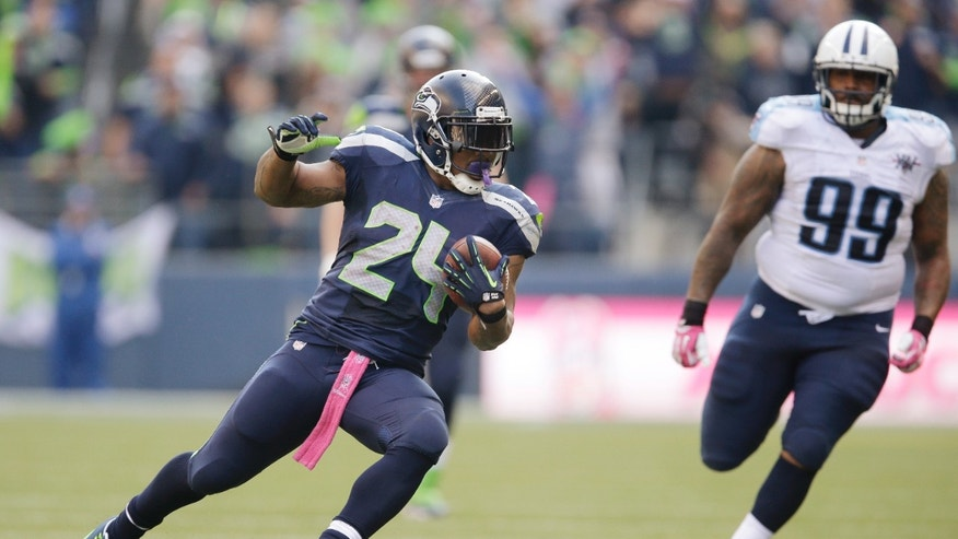 Seattle Seahawks' Marshawn Lynch (24) runs with the ball as Tennessee Titans' Jurrell Casey follows in the second half of an NFL football game, Sunday, Oct. 13, 2013, in Seattle. (AP Photo/Elaine Thompson)