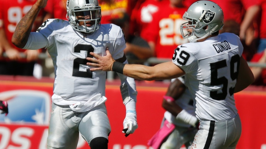 Oakland Raiders quarterback Terrelle Pryor (2) is congratulated by long snapper Jon Condo (59) after a touchdown pass during the first half of an NFL football game against the Kansas City Chiefs at Arrowhead Stadium in Kansas City, Mo., Sunday, Oct. 13, 2013. (AP Photo/Ed Zurga)