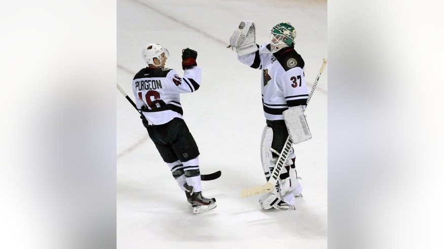 Minnesota Wild defenseman Jared Spurgeon (46) celebrates with goaltender Josh Harding (37) after third period of an NHL hockey game against the Buffalo Sabres in Buffalo, N.Y., Monday, Oct. 14, 2013. Minnesota won 2-1.  (AP Photo/Gary Wiepert)
