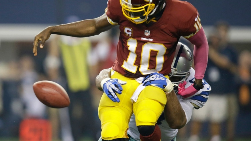 Washington Redskins quarterback Robert Griffin III (10) loses the ball after being sacked by Dallas Cowboys defensive tackle Jason Hatcher in the second half of an NFL football game, Sunday, Oct. 13, 2013, in Arlington, Texas. The Redskins recovered the fumble.  (AP Photo/Tim Sharp)