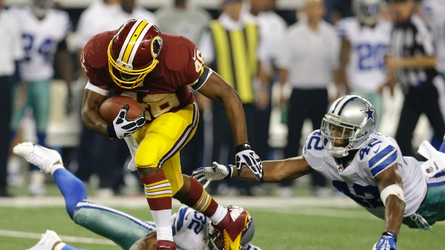 Washington Redskins running back Alfred Morris (46) escapes tackles by Dallas Cowboys' Orlando Scandrick (32) and Barry Church (42) as Morris heads to the end zone for a touchdown in the second half of an NFL football game, Sunday, Oct. 13, 2013, in Arlington, Texas. (AP Photo/LM Otero)