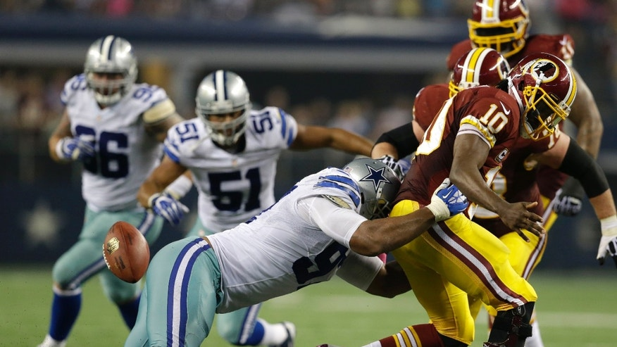 Dallas Cowboys defensive tackle Jason Hatcher sacks Washington Redskins quarterback Robert Griffin III (10) causing him to fumble the ball in the second half of an NFL football game, Sunday, Oct. 13, 2013, in Arlington, Texas. The Redskins recovered the fumble on the play. (AP Photo/LM Otero)