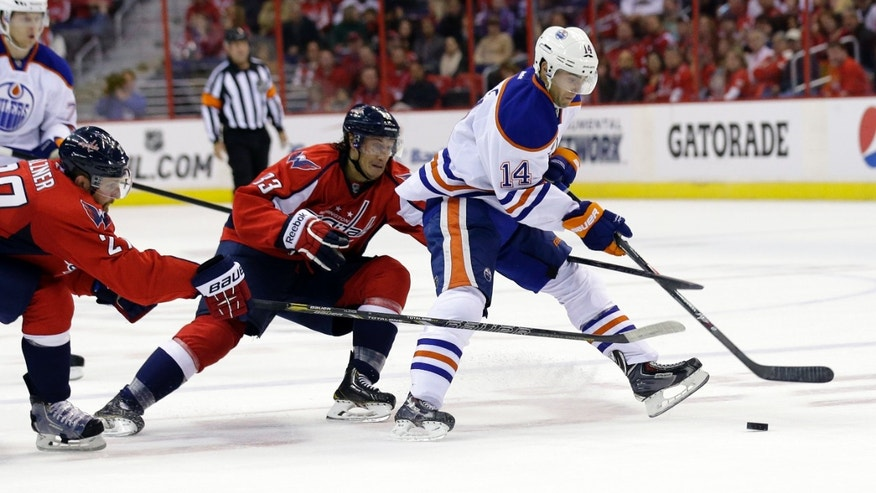 Edmonton Oilers center Jordan Eberle (14) tries to get away from Washington Capitals defenseman Karl Alzner (27) and center Jay Beagle (83) in the second period of an NHL hockey game, Monday, Oct. 14, 2013, in Washington . (AP Photo/Alex Brandon)