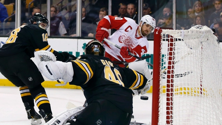 Detroit Red Wings center Henrik Zetterberg (40) shoots and scores against Boston Bruins goalie Tuukka Rask (40) as Bruins right wing Reilly Smith (18) defends, at left, in the first period of an NHL hockey game in Boston, Monday, Oct. 14, 2013. (AP Photo/Elise Amendola)