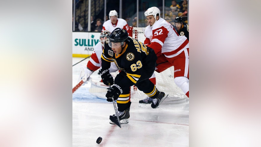 Boston Bruins left wing Brad Marchand (63) looks to pass the puck against the defense of Detroit Red Wings defenseman Jonathan Ericsson (52) in the second period of an NHL hockey game in Boston, Monday, Oct. 14, 2013. (AP Photo/Elise Amendola)
