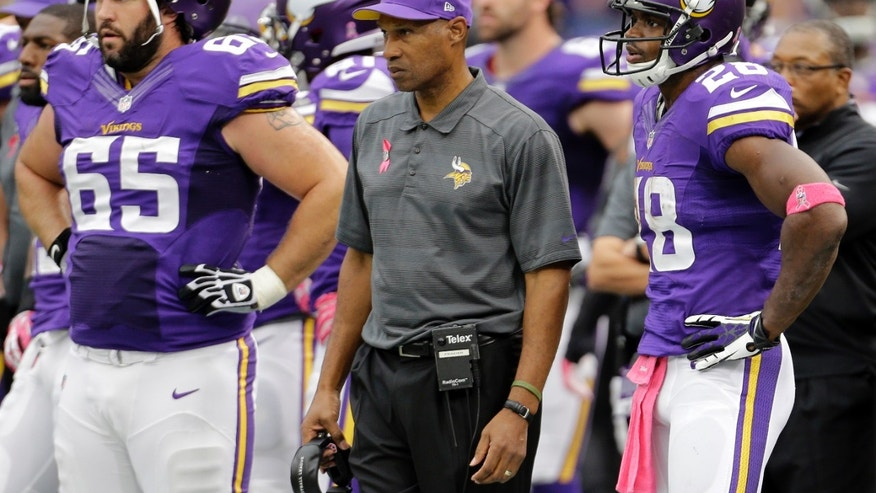 Minnesota Vikings head coach Leslie Frazier, center, along with center John Sullivan (65) and running back Adrian Peterson (28) watch from the sidelines during the first half of an NFL football game against the Carolina Panthers in Minneapolis, Sunday, Oct. 13, 2013. (AP Photo/Ann Heisenfelt)