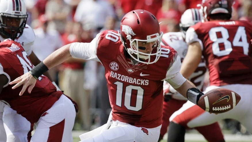 Arkansas quarterback Brandon Allen (10) hands off during the second quarter of an NCAA college football game against South Carolina in Fayetteville, Ark., Saturday, Oct. 12, 2013. (AP Photo/Danny Johnston)