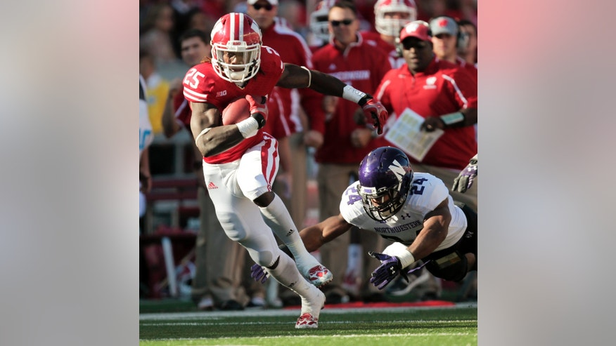 Wisconsin running back Melvin Gordon runs for a first yard against Northwestern safety Ibraheim Campbell during the first half of an NCAA college football game in Madison, Wis., Saturday, Oct. 12, 2013. Wisconsin upset Northwestern 35-6. Gordon had 176 yards. (AP Photo/Andy Manis)