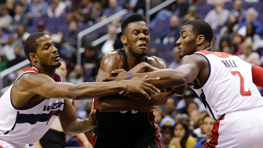 Miami Heat guard Norris Cole (30) drives between Washington Wizards forward Trevor Ariza (1) and guard John Wall (2) in the first half of a preseason NBA basketball game Tuesday, Oct. 15, 2013, in Washington. (AP Photo/Alex Brandon)