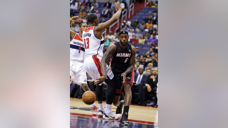 Miami Heat forward LeBron James (6) passes the ball past Washington Wizards forward Kevin Seraphin (13), from France, in the first half of a preseason NBA basketball game Tuesday, Oct. 15, 2013, in Washington. (AP Photo/Alex Brandon)