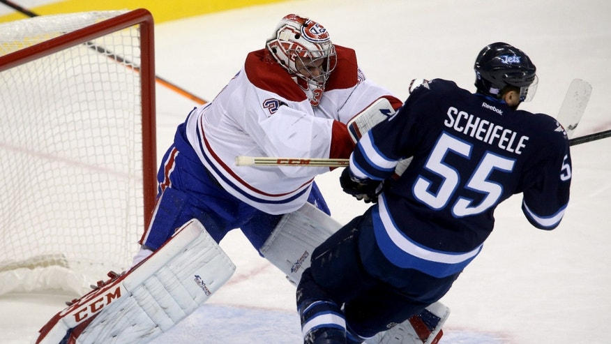 Montreal Canadiens' goaltender Carey Price (31) checks Winnipeg Jets' Mark Scheifele (55) after Scheifele skated into the crease during the first period of an NHL hockey game in Winnipeg, Manitoba, Tuesday, Oct. 15, 2013. (AP Photo/The Canadian Press, Trevor Hagan)