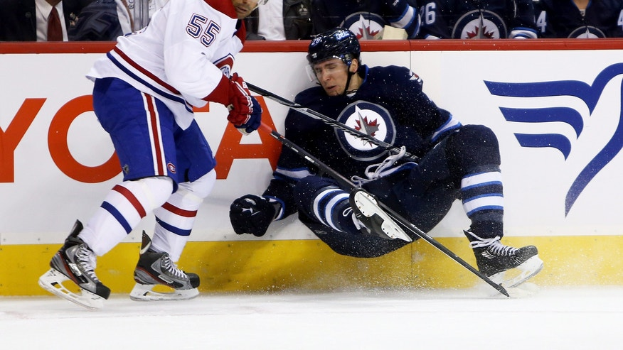 Montreal Canadiens' Francis Bouillon (55) trips up Winnipeg Jets' Blake Wheeler (26) during the second period of an NHL hockey game in Winnipeg, Manitoba, Tuesday, Oct. 15, 2013. (AP Photo/The Canadian Press, Trevor Hagan)
