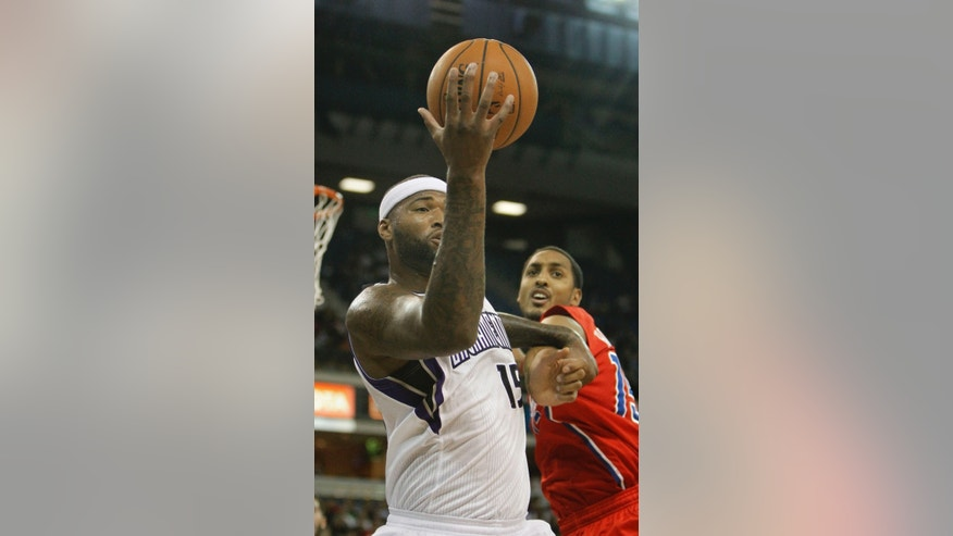 Sacramento Kings center DeMarcus Cousins, left, fouls Los Angeles Clippers center Ryan Hollins as they go after a rebound during the  first quarter of an NBA preseason basketball game in Sacramento, Calif., Monday, Oct. 14, 2013.(AP Photo/Rich Pedroncelli)