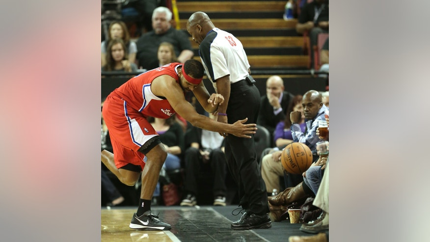 Los Angeles Clippers  forward Jared Dudley collides with official Derek Richardson as he chases the ball during the first quarter against the Sacramento Kings in a NBA preseason basketball game  in Sacramento, Calif., Monday, Oct. 14, 2013.(AP Photo/Rich Pedroncelli)