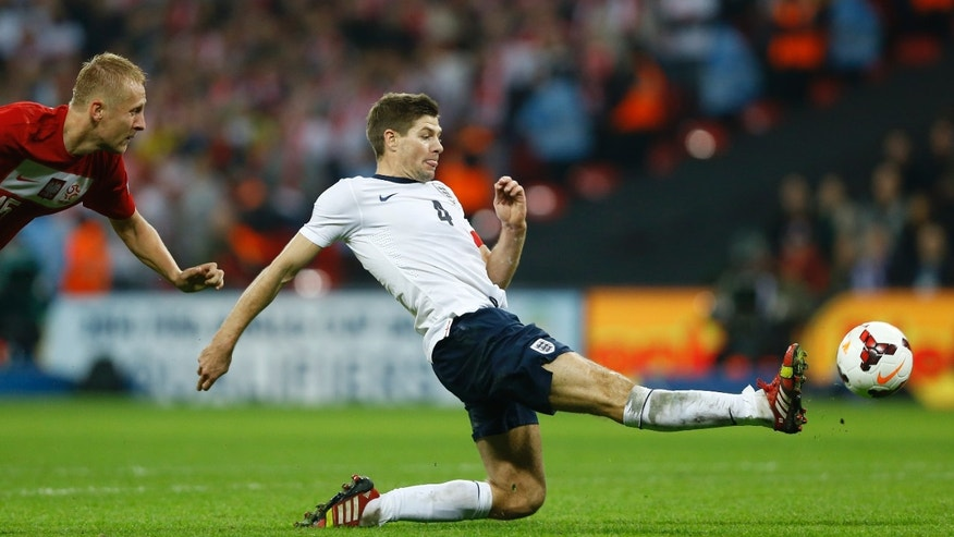 England's Steven Gerrard, right, scores the second goal of the game as Poland's Kamil Glik looks on during the World Cup Group H qualification soccer match between England and Poland at Wembley stadium in London, Tuesday, Oct. 15, 2013. (AP Photo/Kirsty Wigglesworth)