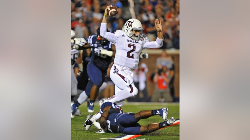 Texas A&M quarterback Johnny Manziel (2) avoids a Mississippi defender during the first half of an NCAA college football game on Saturday, Oct. 12, 2013, in Oxford, MS. #9 Texas A&M won 41-38. (AP Photo/ The Daily Mississippian, Austin McAfee)