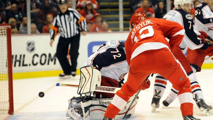 Detroit Red Wings center Pavel Datsyuk backhands the puck past Columbus Blue Jacket's goalie Sergei Bobrovsky for a power play goal during the second period of an NHL hockey game at Joe Louis Arena in Detroit, Tuesday, Oct. 15, 2013.(AP Photo/Lon Horwedel)