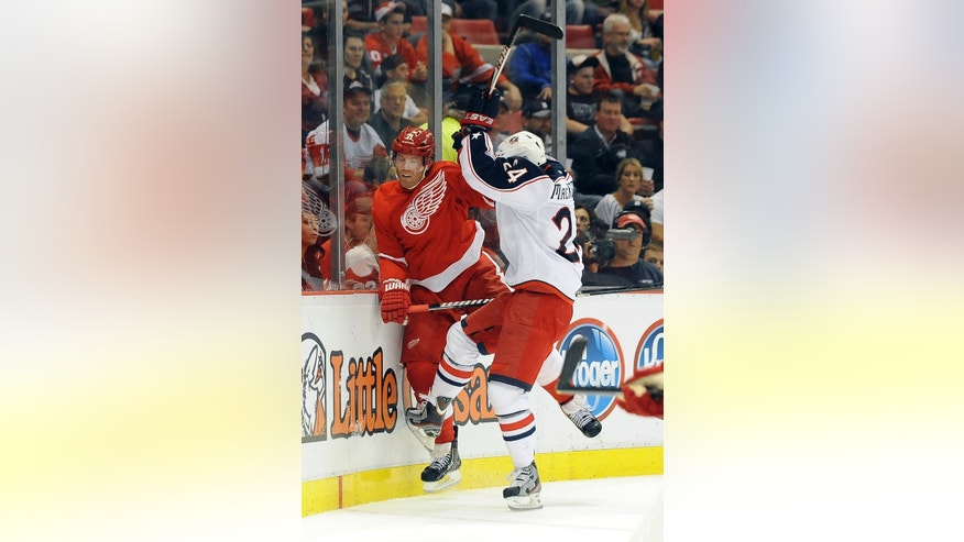 Detroit Red Wings right winger Daniel Cleary, left, gets checked into the boards by Columbus Blue Jackets center Derek MacKenzie during the second period of an NHL hockey game at Joe Louis Arena in Detroit, Tuesday, Oct. 15, 2013.(AP Photo/Lon Horwedel)