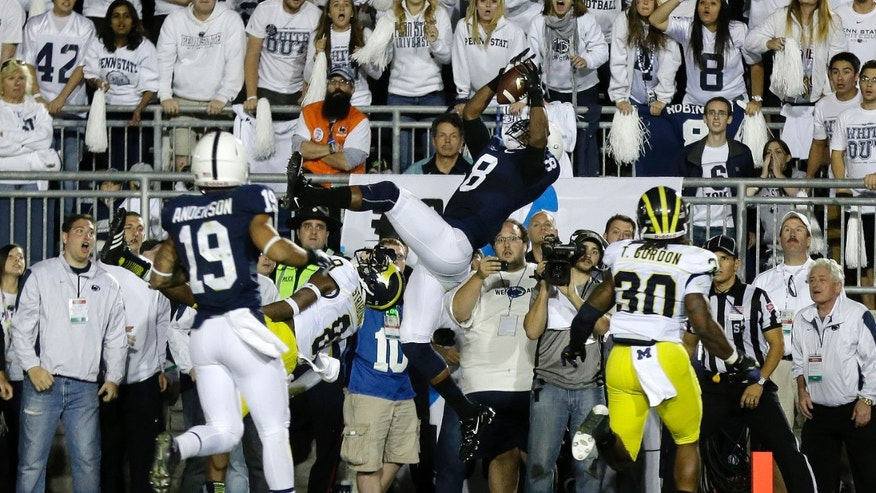 Penn State wide receiver Allen Robinson (8) catches a pass from Penn State quarterback Christian Hackenberg (14) over Michigan defensive back Channing Stribling (8) during the fourth quarter of an NCAA college football game in State College, Pa., Saturday, Oct. 12, 2013. Penn State won 43-40. (AP Photo/Gene J. Puskar)