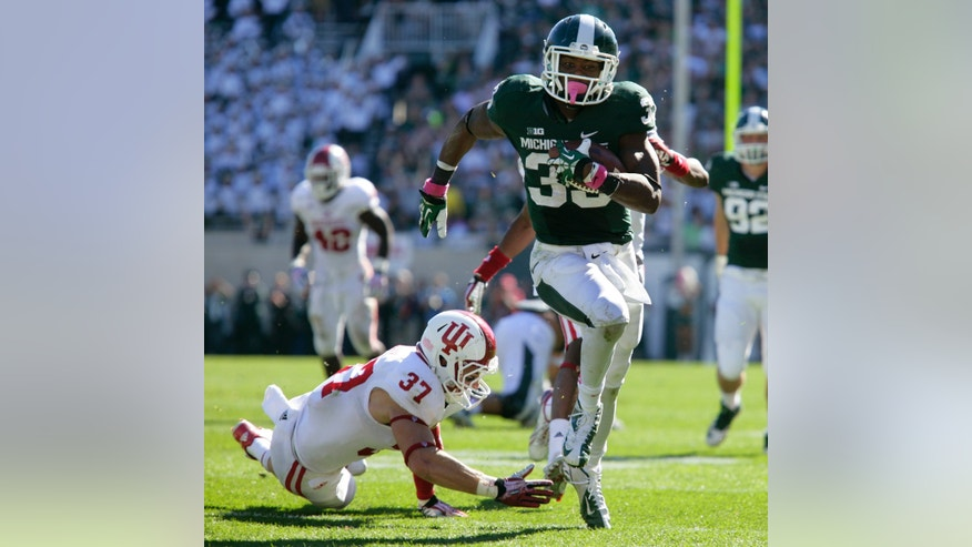 Michigan State's Jeremy Langford, right, runs past Indiana's Mark Murphy (37) for a 32-yard touchdown during the third quarter of an NCAA college football game, Saturday, Oct. 12, 2013, in East Lansing, Mich. Michigan State won 42-28. (AP Photo/Al Goldis)