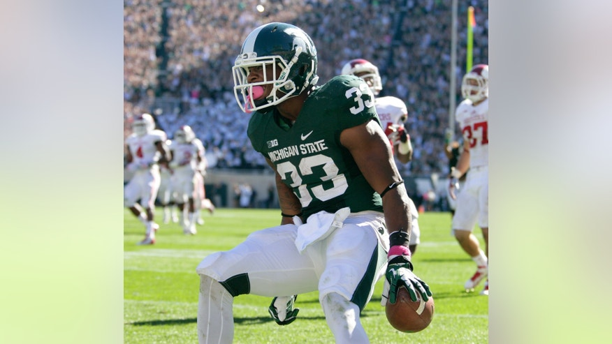 FILE - In this Oct. 12, 2013 file photo, Michigan State's Jeremy Langford (33) celebrates his 32-yard touchdown during the third quarter of an NCAA college football game against Indiana, in East Lansing, Mich. Langford lifted Michigan State's offense with four touchdowns against Indiana. The question now is whether he's ready to shoulder a bigger workload for the Spartans, who had to replace star running back Le'Veon Bell this year. (AP Photo/Al Goldis, File)