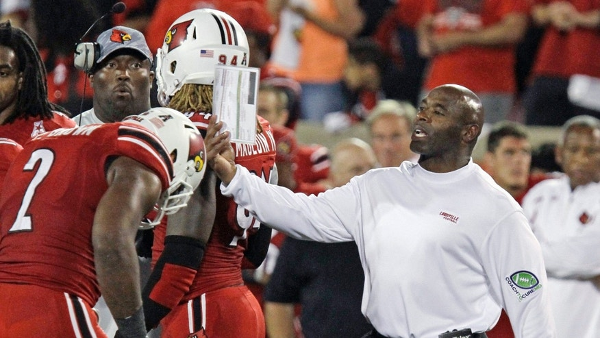 Louisville coach Charlie Strong directs his team during a timeout in their NCAA college football game against Rutgers in Louisville, Ky., Thursday, Oct. 10, 2013. Louisville remained undefeated with a 24-10 victory. (AP Photo/Garry Jones)