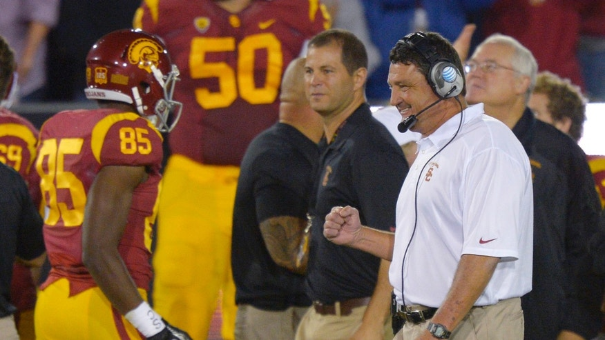 Southern California interim coach Ed Orgeron, right, celebrates after USC scored a touchdown during the first half of an NCAA college football game against Arizona, Thursday, Oct. 10, 2013, in Los Angeles. (AP Photo/Mark J. Terrill)