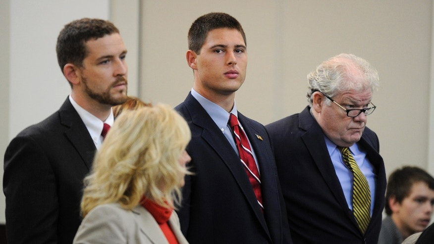 Former Vanderbilt football player Brandon Vandenburg, center, stands with his attorneys Nathan Colburn, left, and David King, right, during a discussion hearing at the Birch Building Wednesday, Oct. 16, 2013 in Nashville, Tenn. Attorneys set a trial date of Aug. 11 on Wednesday for Vandenburg, of Indio, Calif., and Cory Batey, of Nashville, two former Vanderbilt football players charged with raping an unconscious fellow student. Two other ex-players, Brandon Banks, of Brandywine, Md., and Tip McKenzie, of Woodville, Miss., are also charged with rape in the June 23 incident. Their cases were separated from the other two players on Wednesday.  (AP Photo/The Tennessean, Sanford Myers)