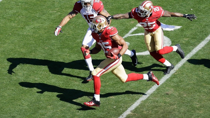 San Francisco 49ers safety Eric Reid (35) runs past cornerback Tarell Brown (25) and Arizona Cardinals wide receiver Michael Floyd (15) after intercepting quarterback Carson Palmer during the first quarter of an NFL football game in San Francisco, Sunday, Oct. 13, 2013. (AP Photo/Ben Margot)