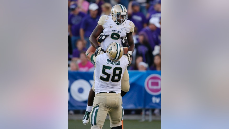 Baylor running back Glasco Martin (8) celebrates a touchdown with offensive linesman Spencer Drango (58) during the second half of an NCAA college football game against Kansas State in Manhattan, Kan., Saturday, Oct. 12, 2013. Baylor defeated Kansas State 35-25. (AP Photo/Orlin Wagner)