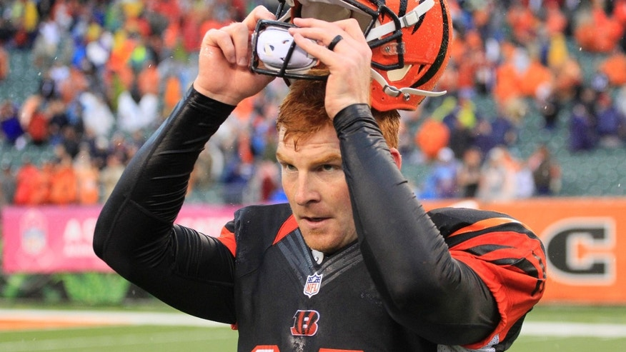FILE - In this Oct. 6, 2013 file photo, Cincinnati Bengals quarterback Andy Dalton takes off his helmet after the Bengals beat the New England Patriots 13-16 in an NFL football game, in Cincinnati. Dalton is getting it done, leading the Bengals to first place in the AFC North. (AP Photo/Tom Uhlman, File)
