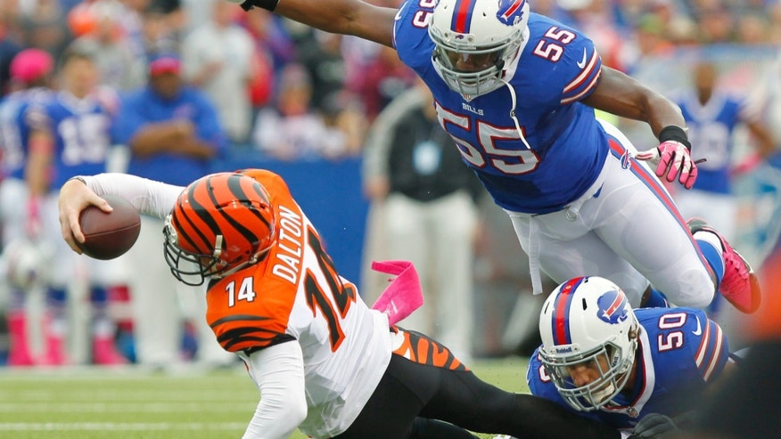 Cincinnati Bengals quarterback Andy Dalton (14) stretches for more yardage as Buffalo Bills outside linebacker Jerry Hughes (55) dives towards him in the first quarter of the NFL football game on Sunday, Oct. 13, 2013, in Orchard Park, N.Y. (AP Photo/Bill Wippert)
