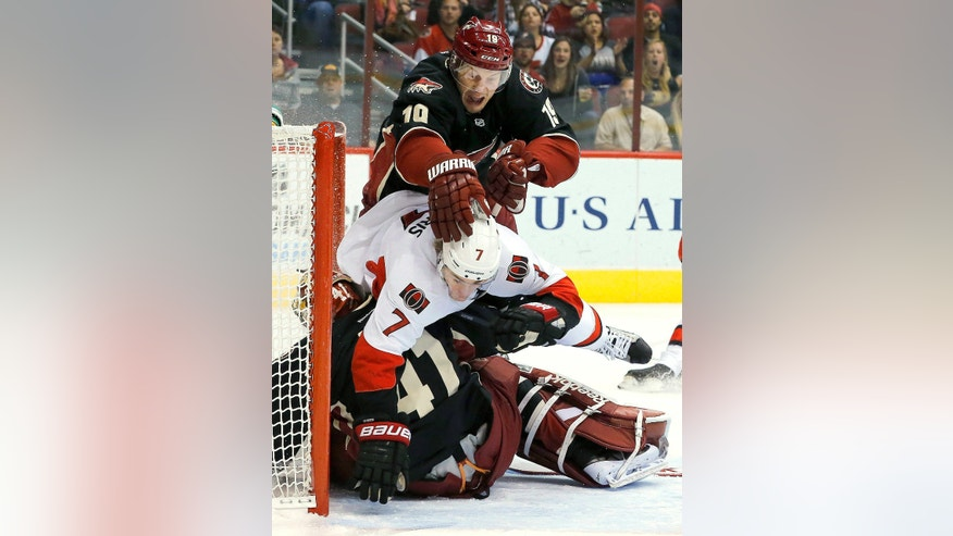 Ottawa Senators' Kyle Turris (7) plows into Phoenix Coyotes' Mike Smith (41) as Coyotes' Shane Doan (19) shoves Turris during the first period in an NHL hockey game Tuesday, Oct. 15, 2013, in Glendale, Ariz. Turris received an interference penalty on the play. (AP Photo/Ross D. Franklin)