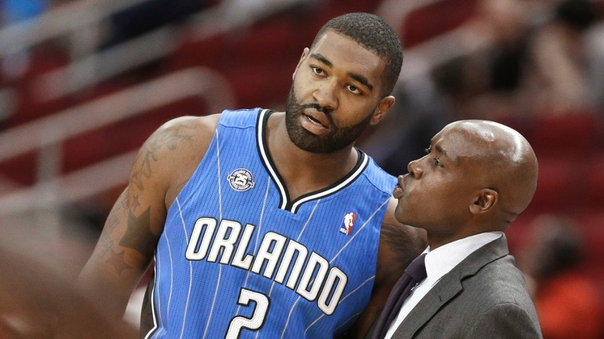 Orlando Magic coach Jacque Vaughn talks with Kyle O'Quinn during the first half of an NBA preseason basketball game against the Houston Rockets on Wednesday, Oct. 16, 2013, in Houston. (AP Photo/Pat Sullivan)