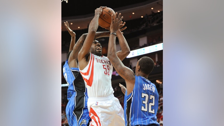 Houston Rockets' Reggie Williams (55) is fouled by Orlando Magic's Solomon Jones, left, as Kris Joseph (32) defends during the second half of a preseason NBA  basketball game Wednesday, Oct. 16, 2013, in Houston. (AP Photo/Pat Sullivan)