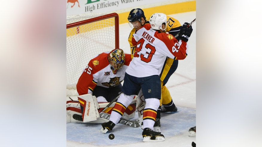 Florida Panthers goalie Jacob Markstrom (25), of Sweden, Nashville Predators forward Patric Hornqvist (27), of Sweden, and Florida Panthers defenseman Mike Weaver battle for the puck in the second period of an NHL hockey game on Tuesday, Oct. 15, 2013, in Nashville, Tenn. (AP Photo/Mark Zaleski)