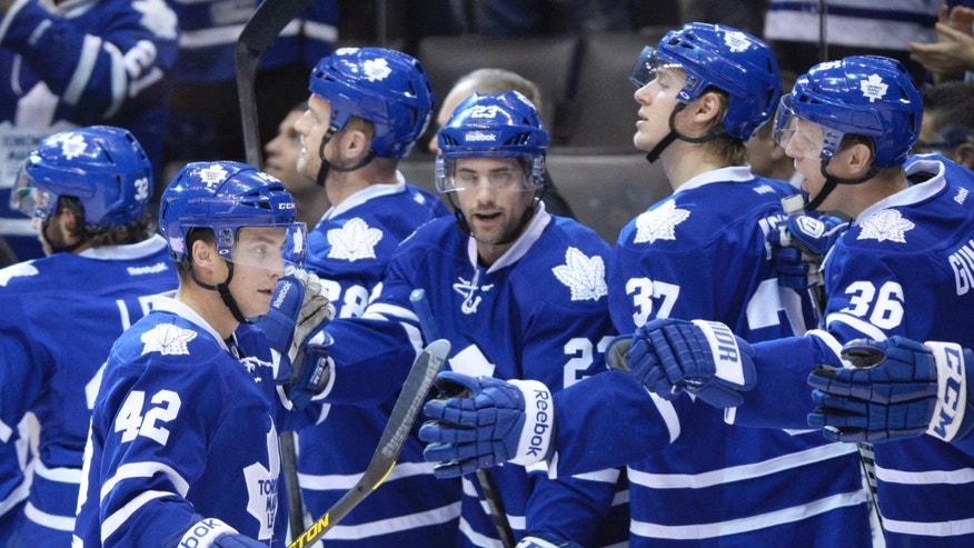 Toronto Maple Leafs forward Tyler Bozak is congratulated on his goal by teammates Trevor Smith, center, Carter Ashton, second from right, and Carl Gunnarsson, right, during the first period of an NHL hockey game against the Minnesota Wild in Toronto on Tuesday, Oct. 15, 2013. (AP Photo/The Canadian Press, Frank Gunn)