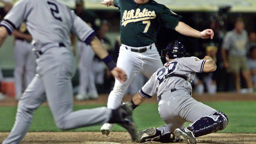 FILE - In this Oct. 13, 2001, file photo, Oakland Athletics' Jeremy Giambi, center, is tagged out at home by New York Yankees' Jorge Posada, right, during Game 3 of the American League Division Series, in Oakland, Calif.  Giambi tried to score from first on a double from Terrence Long in the seventh inning, but Yankees shortstop Derek Jeter assisted with a throw from between first and home for the out.  (AP Photo/Eric Risberg, File)