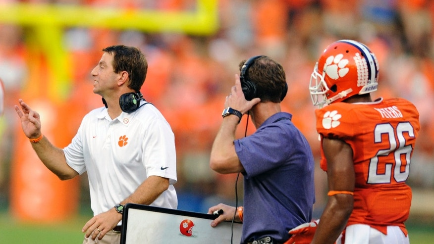 Clemson head coach Dabo Swinney, left, calls out a play to his team while defensive coordinator Brent Venables, center, and Garry Peters watch during the second half of an NCAA college football game against Boston College, Saturday, Oct. 12, 2013, at Memorial Stadium in Clemson, S.C. Clemson won 24-14. (AP Photo/ Richard Shiro)