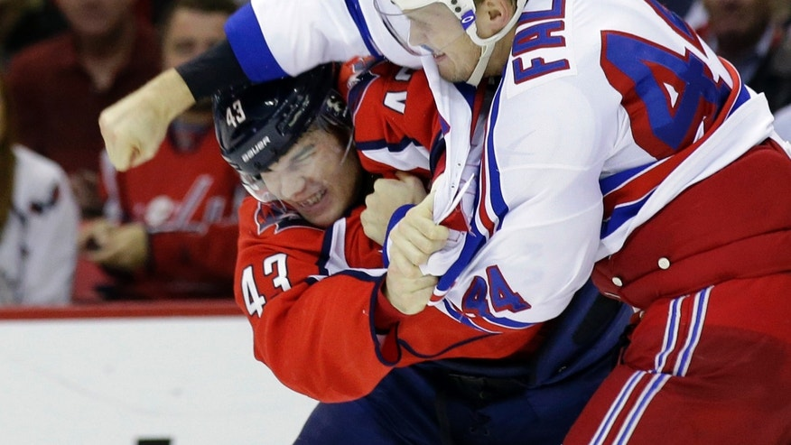 Washington Capitals right wing Tom Wilson, left, ducks a punch by New York Rangers defenseman Justin Falk as they fight in the first period of an NHL hockey game, Wednesday, Oct. 16, 2013, in Washington. (AP Photo/Alex Brandon)