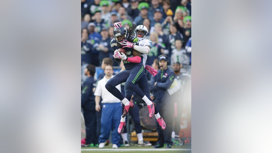 Seattle Seahawks cornerback Richard Sherman (25) intercepts a pass intended for wide receiver Nate Washington, right, in the second half of an NFL football game, Sunday, Oct. 13, 2013, in Seattle. (AP Photo/Scott Eklund)