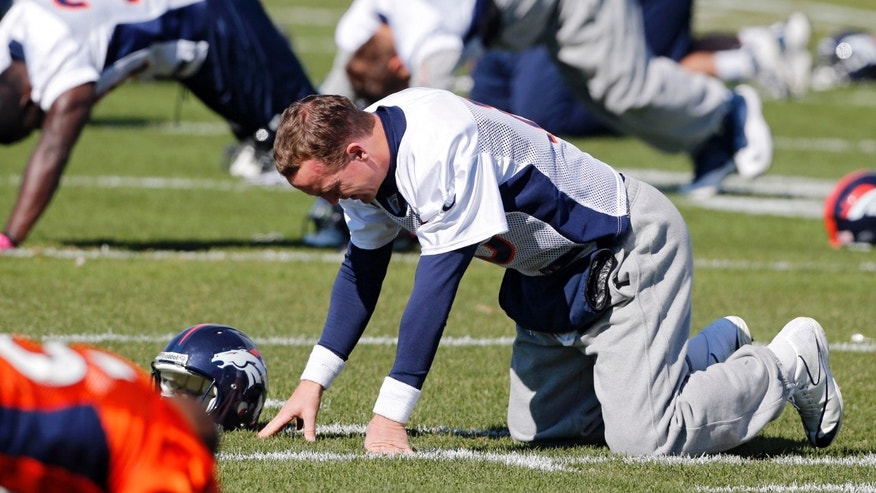 Denver Broncos quarterback Peyton Manning stretches at the NFL football team's practice facility in Englewood, Colo., on Wednesday, Oct. 16, 2013. Manning is expected to lead the Broncos against the Indianapolis Colts this Sunday. (AP Photo/Ed Andrieski)