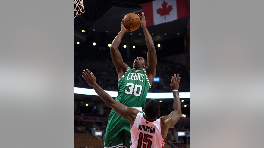 Boston Celtics forward Brandon Bass (30) drives to the hoop as Toronto Raptors forward Amir Johnson defends during the first half of a preseason NBA basketball game in Toronto on Wednesday, Oct. 16, 2013. (AP Photo/The Canadian Press, Frank Gunn)