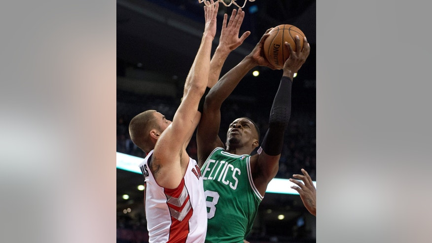 Boston Celtics forward Jeff Green, right, drives to the hoop past Toronto Raptors center Jonas Valanciunas during the first half of a preseason NBA basketball game in Toronto on Wednesday, Oct. 16, 2013. (AP Photo/The Canadian Press, Frank Gunn)