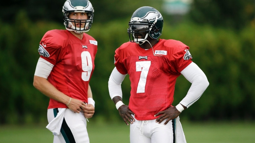 FILE - In this Aug. 6, 2013 file photo, Philadelphia Eagles quarterback Michael Vick (7) and Nick Foles (9) wait to run a drill during a workout in Philadelphia. Fresh off consecutive wins, and easily in the thick of the NFC East race now, the Eagles have a bit of a quarterback controversy brewing. (AP Photo/Matt Slocum, File)