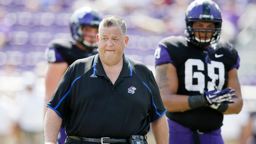 Kansas head coach Charlie Weis walks off the field after checking on an injured payer late in the second half of an NCAA college football game against TCU, Saturday, Oct. 12, 2013, in Fort Worth, Texas. Kansas defensive lineman Peter Gallo (69) watches int he 27-17 TCU win.  (AP Photo/Tony Gutierrez)