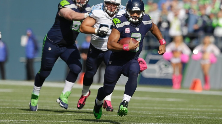 Seattle Seahawks quarterback Russell Wilson, right, runs the ball as Tennessee Titans' Karl Klug, center, and Seahawks' Paul McQuistan, left, pursue during the first half of an NFL football game, Sunday, Oct. 13, 2013, in Seattle. (AP Photo/Elaine Thompson)