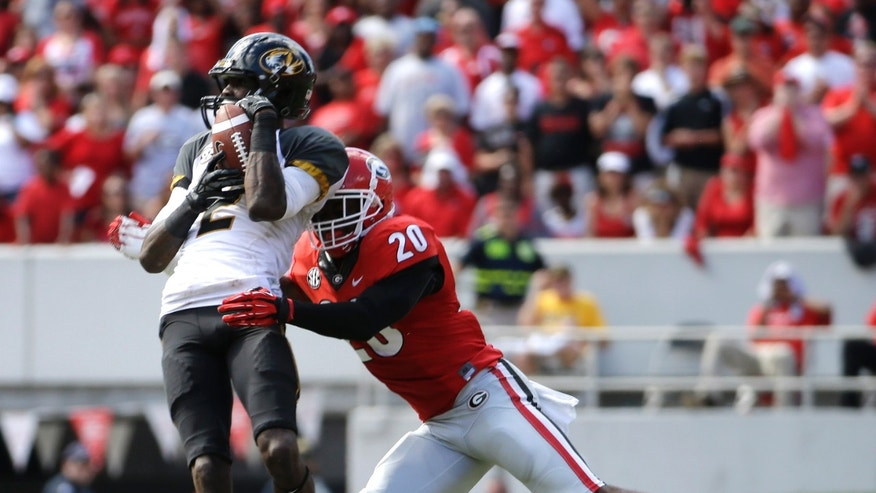 Missouri's L'Damian Washington makes a catch in front of Georgia's Qunicy Mauger (20) during the second half of an NCAA college football game Saturday, Oct. 12, 2013 in Athens, Ga. Missouri won 41-26. (AP Photo/John Bazemore)