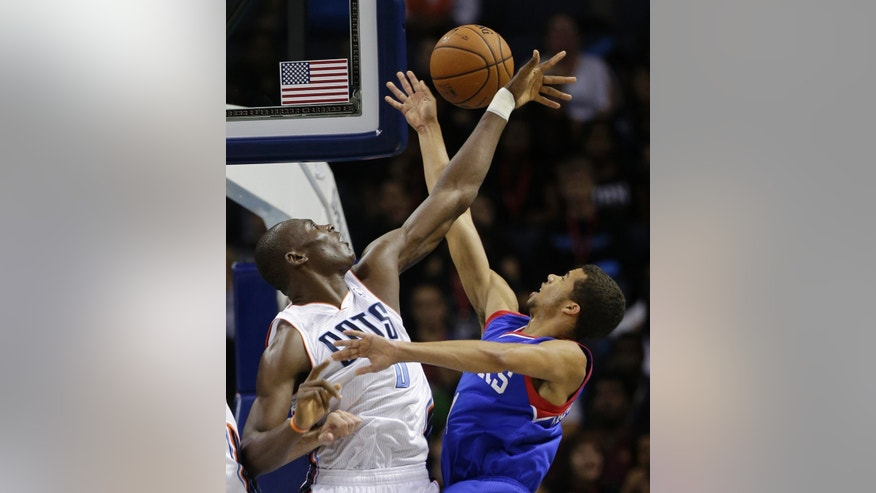 Charlotte Bobcats' Bismack Biyombo, left, blocks a shot by Philadelphia 76ers' Michael Carter-Williams, right, during the first half of a preseason NBA basketball game in Charlotte, N.C., Thursday, Oct. 17, 2013. (AP Photo/Chuck Burton)